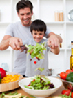Photo of father and son cooking healthy food.
