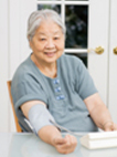Photo of an old woman managing her heart health with a blood pressure cuff.