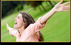 Una mujer en un parque sonríe y sube los brazos al aire