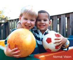 Two young boys holding soccer balls.