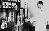Black and white photo of scientist in lab coat working in a laboratory in the 1880s