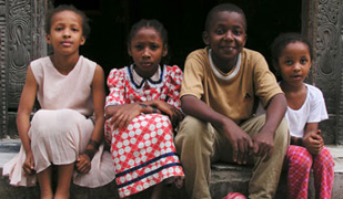 Photo courtesy of World Bank, Four children sit on a doorstep, looking at camera