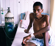 Emaciated man sits up in bed, shirtless, next to large tank with tubes in nose