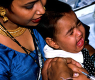 Photo by P. Virot/WHO, Woman holds screaming baby receiving a shot in the arm