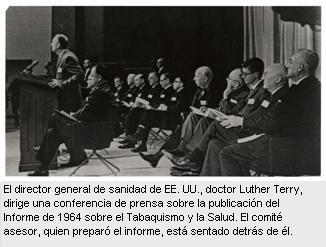 En esta foto en blanco y negro, el director general de sanidad, doctor Luther Terry, se dirige al público de la conferencia de prensa desde el estrado, (el público no aparece en la foto). Dos hileras de hombres están sentados en sillas plegadizas detrás de él.