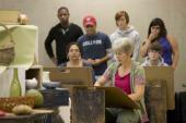 Group looking over teacher's shoulder in art class