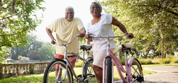 smiling couple holding bicycles in a park
