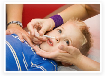 A young boy is getting the nasal spray flu vaccine from his pediatrician