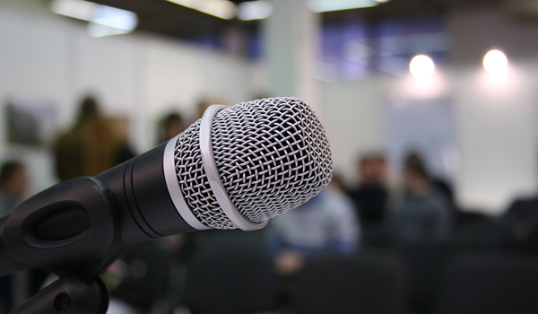 "Focus on a microphone with a blurred mingling audience in the back, signifying ""public comment"""