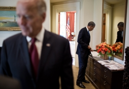President Barack Obama looks at a magazine on the credenza in the Outer Oval Office before departing the White House for a trip, Sept 27, 2012. Vice President Joe Biden talks with an advisor in the foreground. (Official White House Photo by Chuck Kennedy)