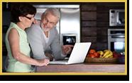 Una pareja busca información la computadora portátil en la cocina de su casa