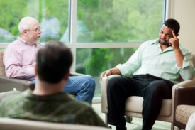 Photo shows three men seated in a circle and engaged in a serious discussion.