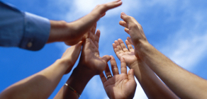 group of diverse hands in the air