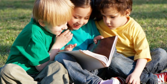 Children reading a book outside.