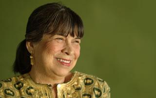 Una mujer con un traje típico mira del lado mientras sonríe