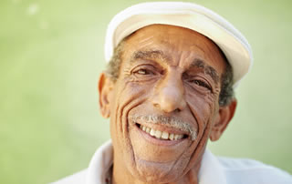 Un hombre mayor con gorro blanco sonríe