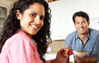 Un hombre y una mujer desayunan cereal con fruta