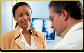 Una mujer sonríe mientras habla con su doctor