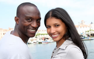 Una pareja joven se paran frente a frente y sonríen a la cámara