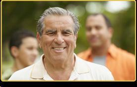 Un hombre con camisa color crema sonríe