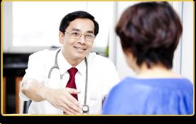Una mujer con camiseta azul habla con su doctor