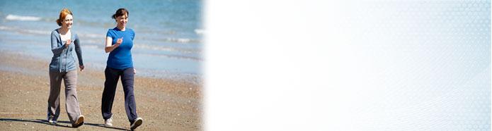 Dos mujeres hacen ejercicio caminando en una playa.