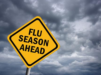 Yellow caution sign reading flu season ahead