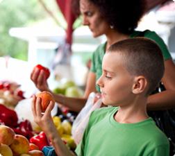 young boy examining a piece of fruit
