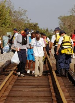 Volunteers walking along railroad tracks