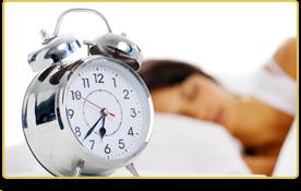 Imagen de un reloj que marca las 6:37. Atrás, una mujer duerme.