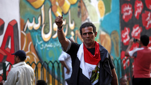 An Egyptian man waves an empty bullet case in front of a mural that was painted on a recently whitewashed wall in Tahrir Square, Cairo.