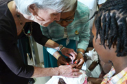 HHS Secretary Sebelius and Haitian Minister of Health Florence Guillaume administer the pentavalent vaccine to a child at the launch of a nationwide vaccine initiative. Credit: Photo by Jean Jacques Augustin.