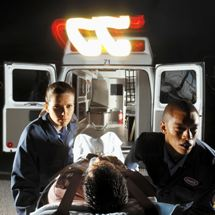Paramedics wheel a patient from an ambulance