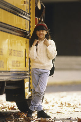 Pretty elementary school age girl is standing next to her school bus.