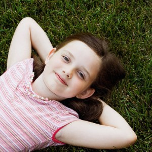A pretty young girl, lying in the grass with her arms behind her head.