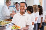Schoolboy holding plate of lunch in school cafeteria smiling at camera