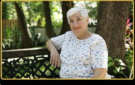 una mujer mayor sentada en la banca de un parque