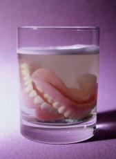 Photograph of dentures in a glass of liquid