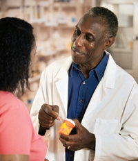 Pharmacist talking to patient with prescription