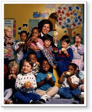 [U.S. Surgeon General Antonia C. Novello in group photo with children at a daycare center]. [1990?].