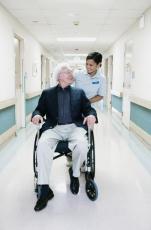 Fotografía de una enfermera asistiendo a un hombre mayor en silla de ruedas