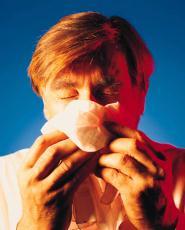 Photograph of a man blowing his nose