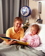 Photograph of a woman reading to a young girl in a hospital bed