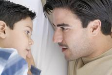 Photograph of a boy and a man talking