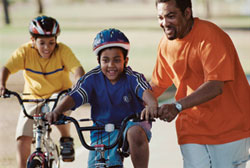 parent helping child ride bicycle