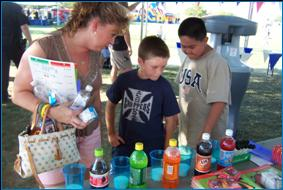 Image of woman and two boys participating in a community event