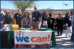 Image of people with Miss Nevada standing behind We Can event table