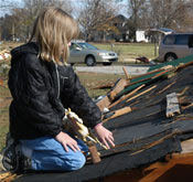 profile of girl holding plastic horse on the destroyed roof of her grandmother's home