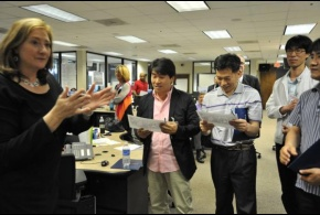 Mary Hudak of FEMA Region IV presents a photo to a group of emergency managers from Korea. The group attended briefings and toured the Regional Response Coordination Center.