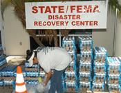a volunteer organzing cases of bottled water